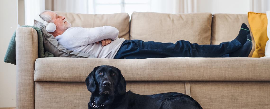 Ein Mieter hört entspannt auf dem Sofa Musik mit Kopfhörer.